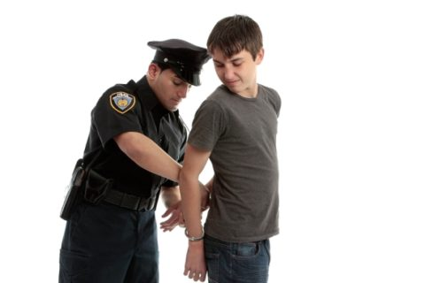 Young teenager getting handcuffed
